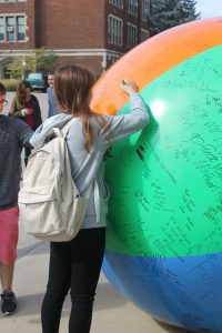 UW Oshkosh students use permanent marker to write messages of their choice on a massive beach ball. The Young Americans for Liberty's First Amendment event took place largely in front of Polk Library.