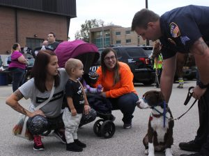 Officer Matt Ziegler shows his dog, Jack, to Allie Ferron and her son, along with Megan Hankwitz. Running With the Cops had multiple service dogs along with horses the attendees could interact with.