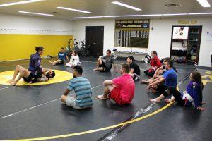 Club President Samuel Gaier demonstrates a Brazilian Jiu-jitsu move on a volunteer club member. Practice takes place in Kolf's wrestling room.