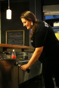 Titan Underground employee Raelena Hoff serves a beer. The Underground now sells alcohol daily.