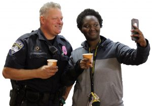 UPD officer Dennis Sabel poses for a selfie with freshman Dasia Harvey at the Coffee with a Cops event.