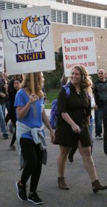 Two participants march with hundreds of others to support survivors of sexual violence.