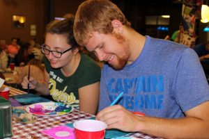 Senior Criminal Justice major Jacob Tennie and Leah Wickland, a senior double majoring in Biology and Art, show off their painting skills at the Painting Class event.