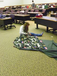 Volunteer Kayla Emhoff makes a tie-blanket to be sent in an active-duty soldier's care package. Her uncle is in the army.