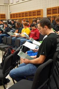 The men's choir group looks over their sheet music in preparation for their performances.