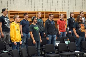 Mens's choir group practices together.