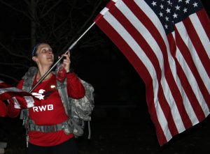 A March For 22 participant displays the American flag during the 2.2 mile walk that started at Dempsey and went through campus.