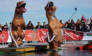 Dressed in an inflatable dinosaur costume, Oshkosh local takes a selfie while jumping into the water.