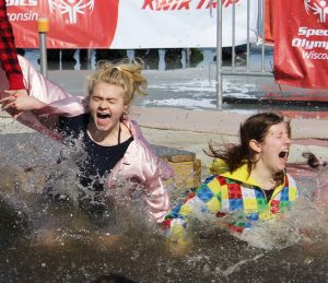 Two friends react to the freezing cold water as they jump into the lake during Saturday's Plunge event.