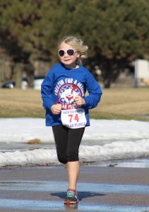 A young girl prepares to cross the finish line at the Freezin' For A Reason 5k Polar Plunge event.