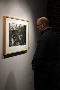 "Former UWO student Michael Wartgo admires Kareken's ""Auto Salvage #1."""