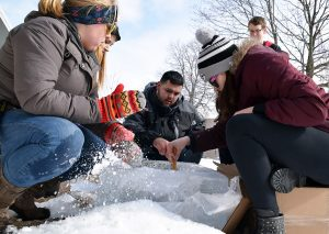 The Reeve Union Board begins to sculpt out a trough for the base of their ice sculpture.