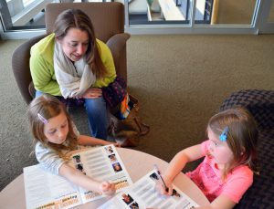 Sarah Bradway plays a matching game with her daughters where they have to match a description to an image of a person that was featured as part of 'Beyond First Impressions.'