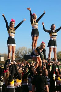 The cheer team performs a stunt at a recent athletic event.