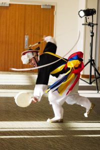 "Dressed in colorful gear, a man performs the ""Sangmo Pankut"" in a Sangmo, a ribboned hat."