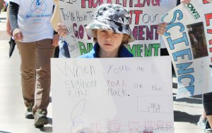 A young boy marches with his sign on Saturday.