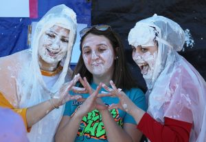 Tri Sigma sorority members Morgan Sternad (left), Alex Thompson (middle) and Cassidy Wichman pose for a photo after Sternad and Wichman unexpectedly splash Thompson with whipped cream.