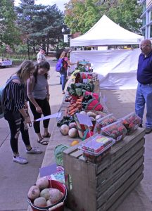 Freshmen Taylor Russell and Tori Wondra examine the prices of produce at Midwest Foods' booth. Adam Brown (right) said he wanted to let students know their produce is fresh in their meals on campus, and that it doesn't come processed.