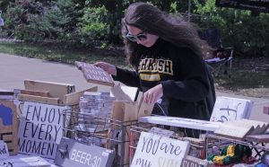Junior Monica Fieck looks through decorative signs at the Sparkles & Sawdust booth.