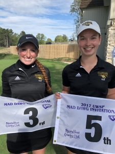 Micayla Richards (left) and Kayla Priebe hold flags from the Stevens Point Country Club after placing in third and fifth places, respectively.