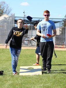 Two friends challenge each other in a bean bag game before the football game against UW-Whitewater.