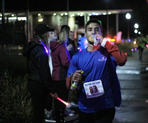 Juan Martinez eats a donut while he runs in the annual Run With the Cops event on campus.