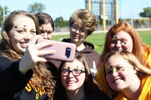 A group of friends take a selfie after getting their faces painted during the Titan Tailgate.
