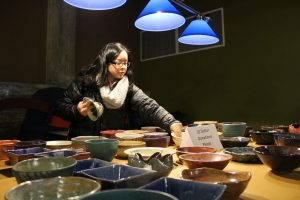 Jessica Martinez peruses bowls that were crafted by the art department for the charity event Empty Bowls.