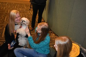 """ABOVE: Liam the therapy dog is all smiles as he helps UWO students forget their stress. LEFT: Two students hug a tiny dog. RIGHT: A student takes a photo of a golden retreiver."""