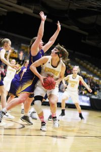 UW Oshkosh senior forward Eliza Campbell ducks under a Pointer player and powers toward the hoop against UW-Stevens Point.