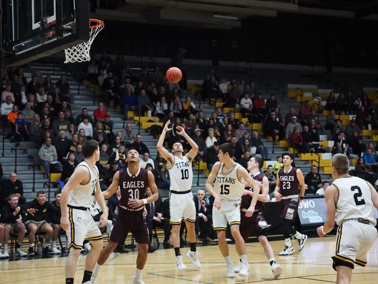 The trio of UW Oshkosh athletes, senior guard Jake Laihnen (10), sophomore forward Adam Fravert (15) and sophomore center Jack Flynn, look to gather in a loose ball against UW-La Crosse. The three combined for 29 points on February 10.