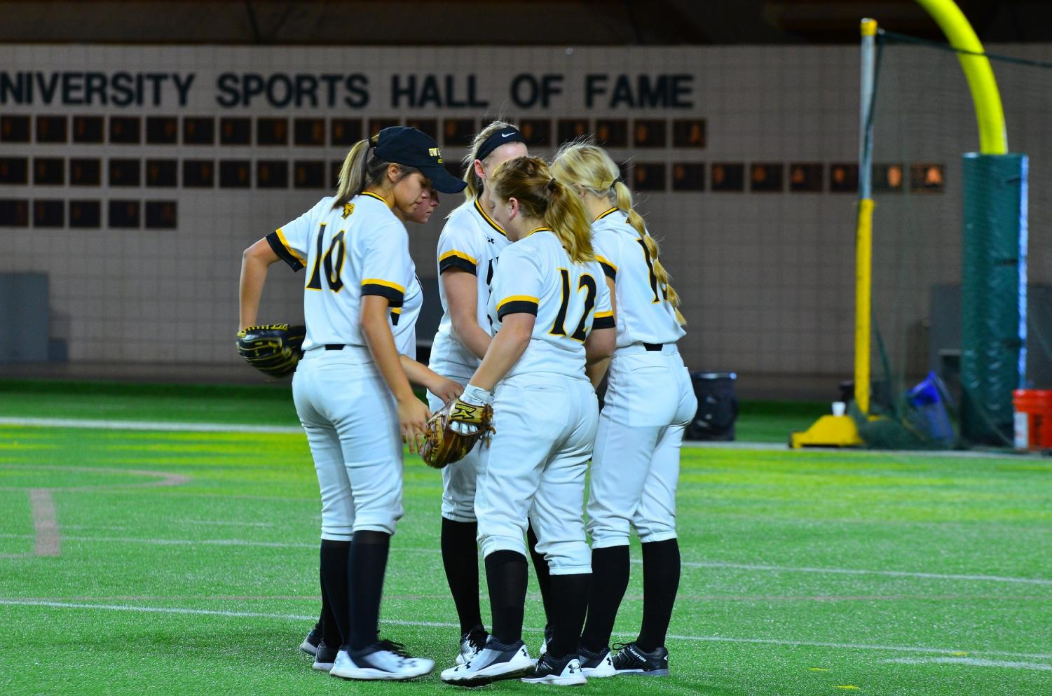 Five UW Oshkosh Titan softball players meet on the field during a pause in the action over the opening weekend in Michigan.