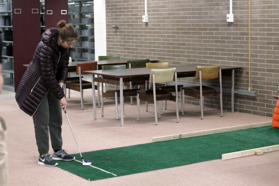 A mini golfer lines up her shot at one of the second-floor holes. The course utilized the library's multiple floors and furniture to create hazards.