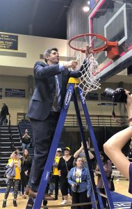 Head coach Pat Juckem cuts the nets in the Augustana gym, celebrating the Titans' first-ever berth in the Final Four.