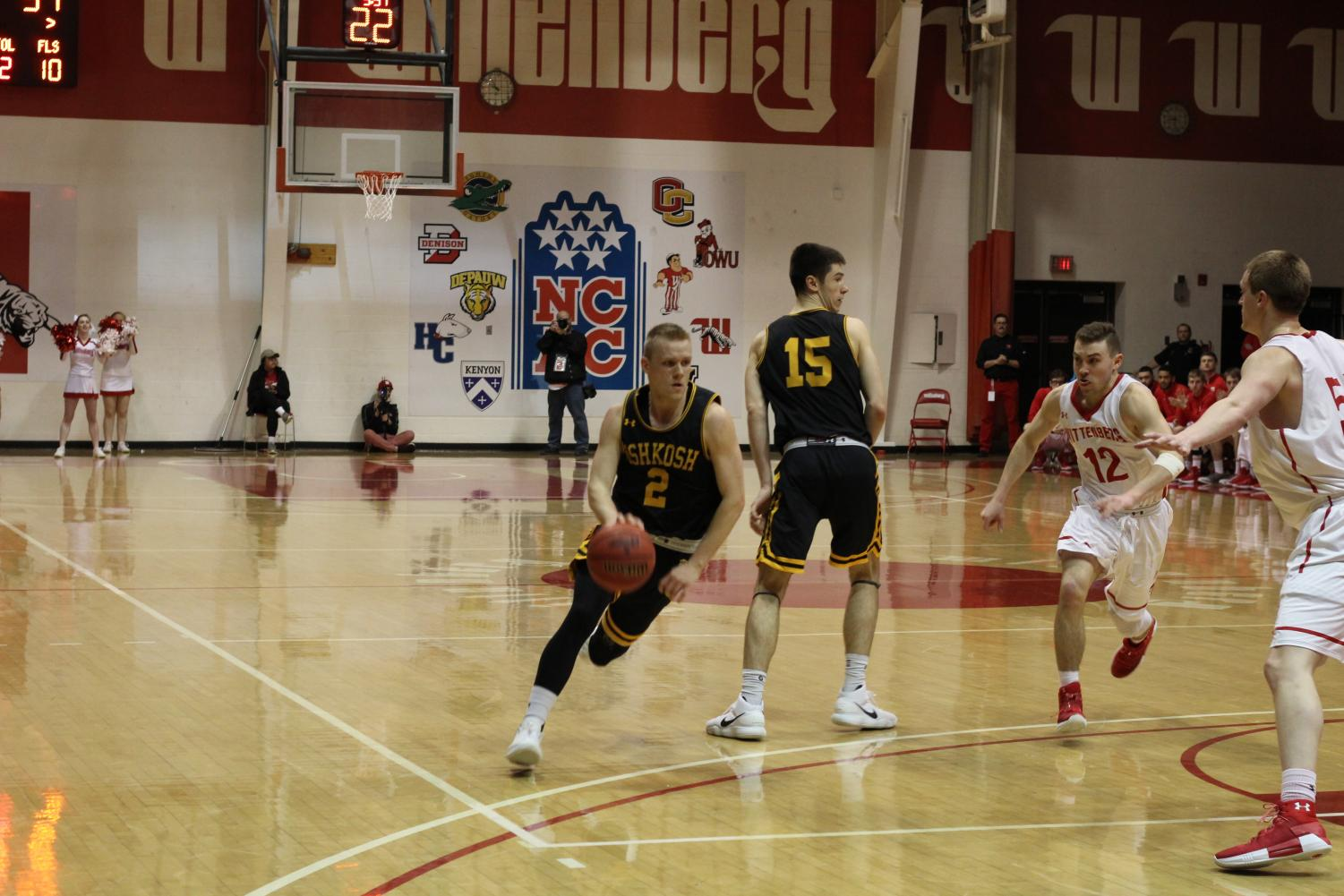 Junior guard Ben Boots (No. 2) drives around a screen set by sophomore forward Adam Fravert (No. 15) during the second round game against Wittenberg University.