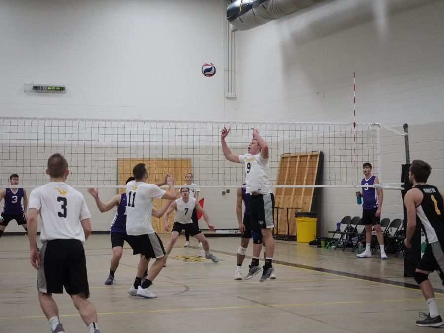 The combination of sophomore setter/right side hitter Nick Davies (No. 9) and senior middle blocker Nate Leitermann (No. 11) work together to set up a successful spike return against the Warhawks.