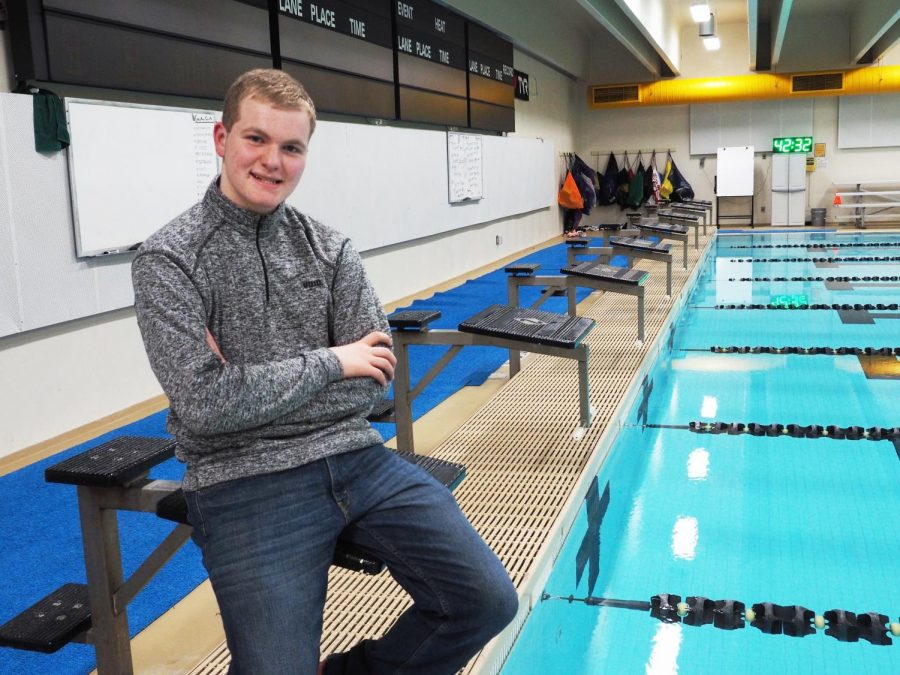High school student Jarod Falk poses on the starting blocks at Albee Pool. Falk uses the pool to train for the Special Olympics USA Games in Seattle, Washington. Members of the men's team volunteer to practice with Falk on their own time.