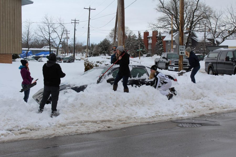 Students work together to dig out a car on High Ave.