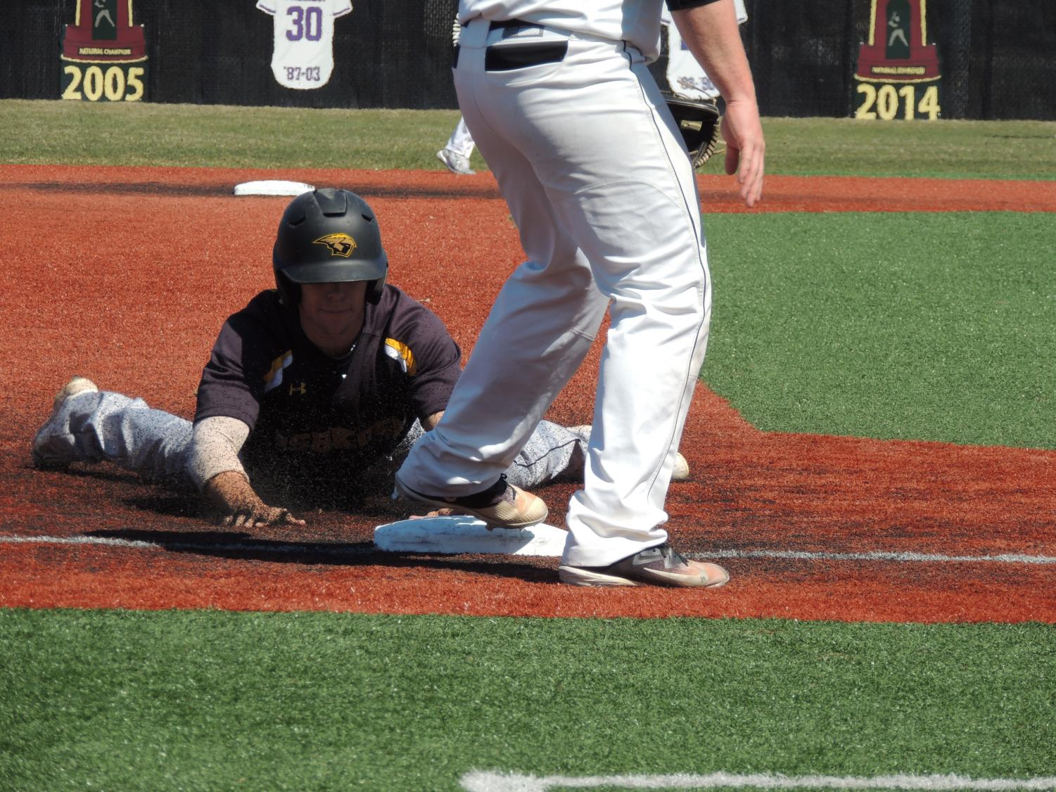 An Oshkosh baserunner slides head first into third base against the UW-Whitewater Warhawks on April 25.