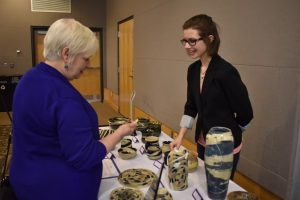 Student shows pottery and answers questions