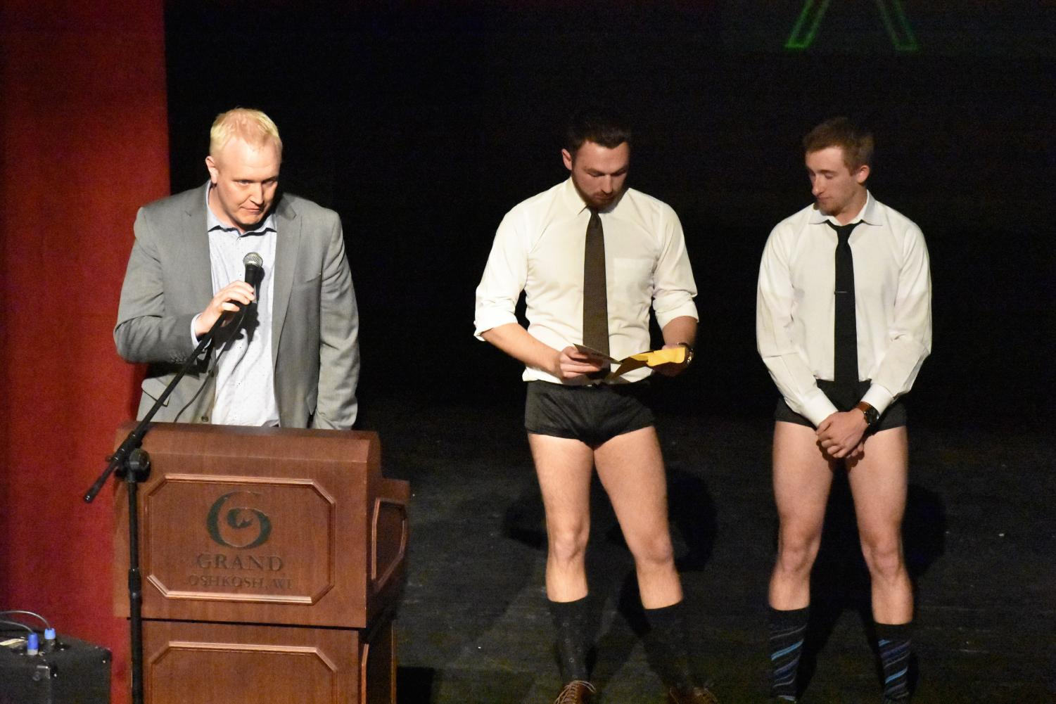 Women's basketball coach Brad Fischer stands on stage alongside two UWO swimmers displaying out-of-the-pool attire on Monday.
