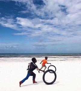Children race broken bicycle rims on the beach in Zanzibar, Tanzania.