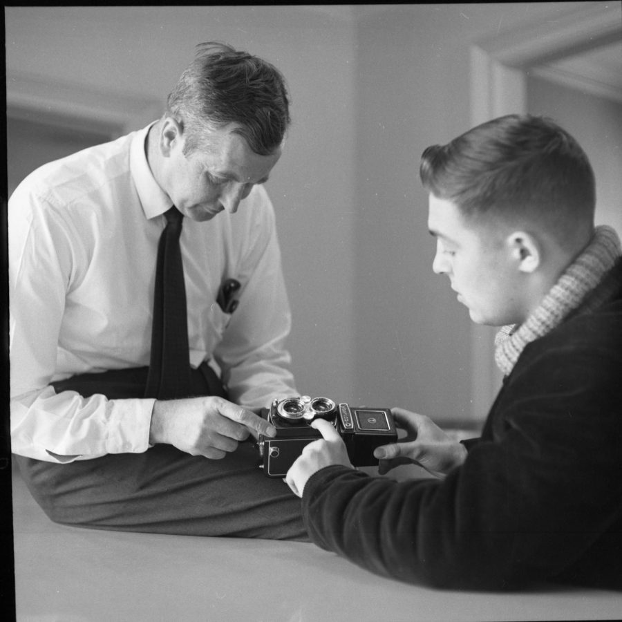 """Dave """"Doc"""" Lippert, who started the journalism dept., teaches a student how to use a camera."""