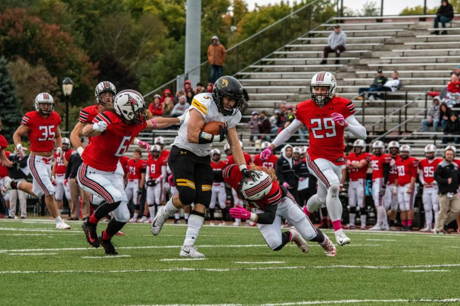 Senior running back Mitch Gerhartz runs down the field while a group of UW-River Falls defenders try to tackle him. Gerhartz finished with 122 yards en route to UW Oshkosh's 48-14 victory. The win took the Titans to 1-0 in the Wisconsin Intercollegiate Athletic Conference as they try reclaim the conference title.