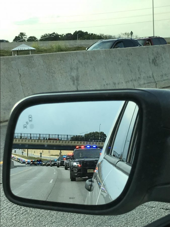 A line of police cars can be seen in the side mirror during rush-hour traffic on I-94 in Milwaukee. The road was shut down to honor a Milwaukee officer killed on duty.