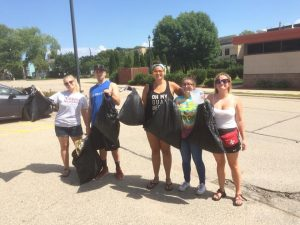 From left, Natalie Kostman, Jeremy Piper, Elizabeth Armstrong, Miklyn Armstrong and Emily Eresh present a large amount of garbage collected during an outing to clean the campus.