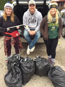 From left, Emily Eresh, William Nebus and Natalie Kostman pose with garbage collector equipment.