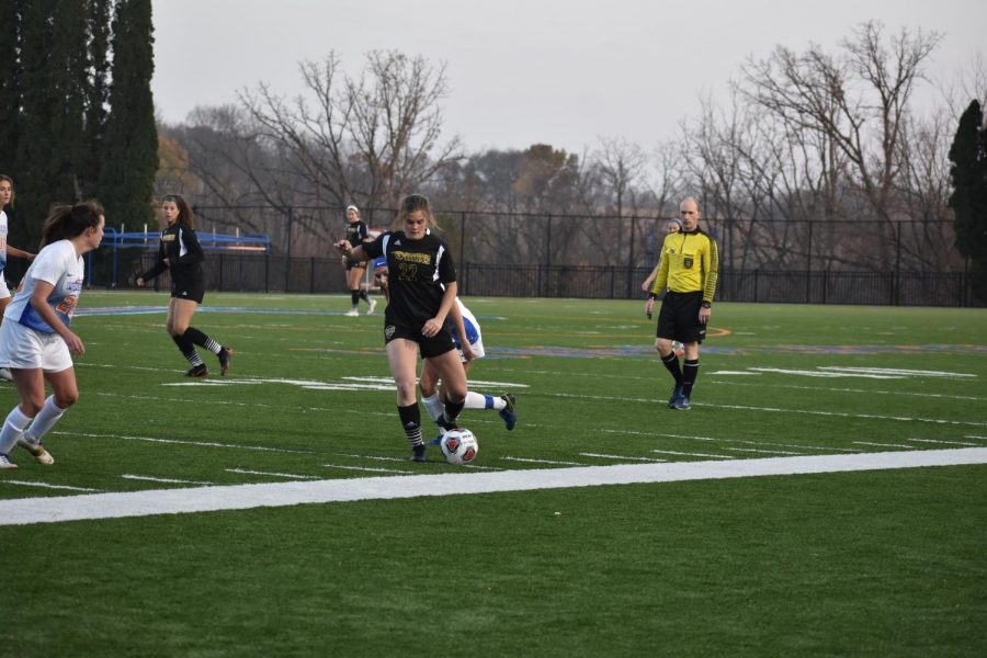 Junior Michaela Schenk dribbles around a defender.