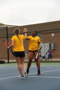 Doubles partners junior Alyssa Leffler and freshman Michelle Spicer congratulate each other on winning a rally.