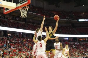 Junior Adam Fravert shoots a hookshot over Badgers Nate Reuvers and Walt McGrory on his way to a team-high 20 points.